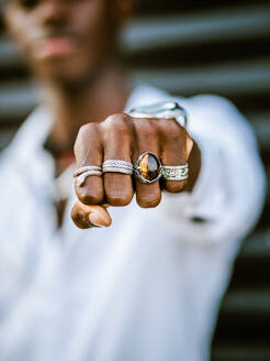 Blurred anonymous African American stylish male showing fist with various trendy silver rings - ADSF19723