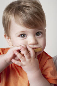 Baby boy in orange t-shirt eating biscuit - ISPF00006