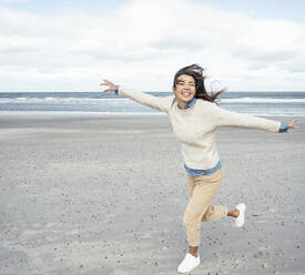 Portrait of young woman running on sandy beach with raised arms - UUF22537