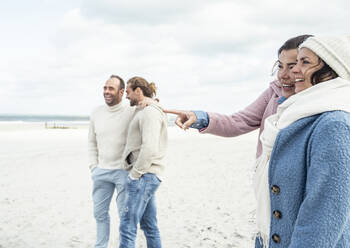 Group of adult friends standing and talking on coastal beach - UUF22552