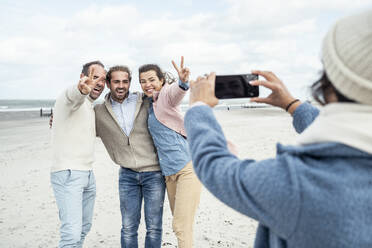 Group of friends taking smart phone photos at beach - UUF22564