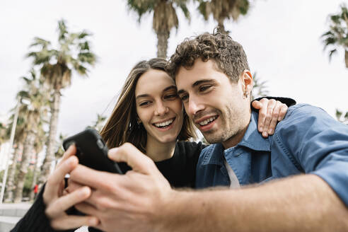 Smiling couple looking at smart phone outdoors - XLGF01021