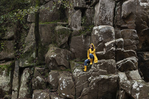 Thoughtful young woman wearing yellow raincoat sitting on rocks in forest - KBF00657