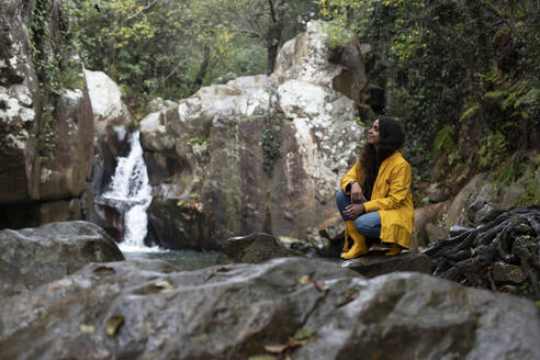 Thoughtful female hiker crouching on rock against waterfall in forest during rainy season - KBF00660