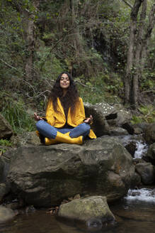 Female hiker wearing yellow raincoat meditating while sitting on rock in forest - KBF00663