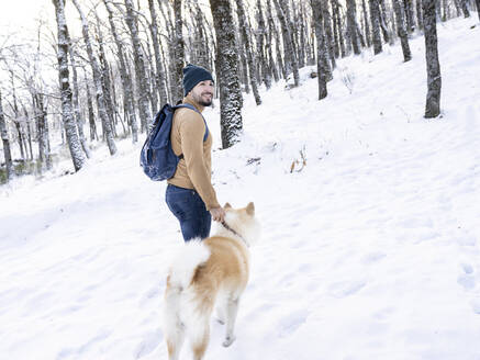 Smiling young man looking away while standing with akita dog in snow covered land - JCCMF00833