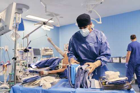 Doctor wearing face mask choosing clothes while standing with colleague at operation room - SASF00137