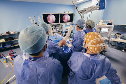 Doctor analyzing endoscope on computer monitor while standing at operating room - SASF00143
