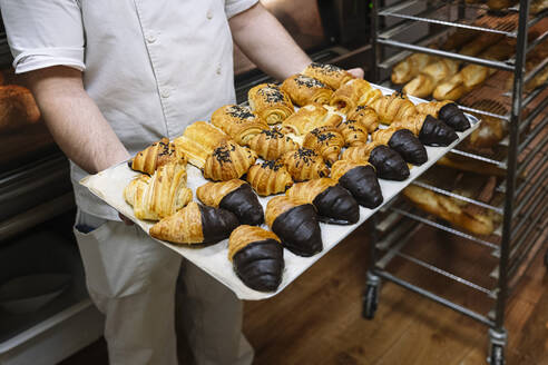 Male chef holding baking sheet filled with croissant in bakery kitchen - JCMF01821