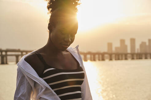 Tranquil pensive young African American female in casual clothes relaxing on urban seafront at sunset time - ADSF19884