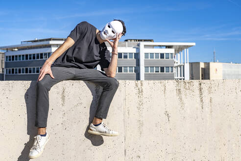 Man wearing white mask looking away while sitting with head in hands on wall - GGGF00818