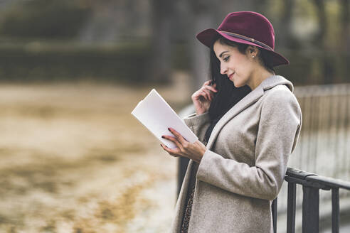 Beautiful woman wearing hat reading book while standing in park - GGGF00836