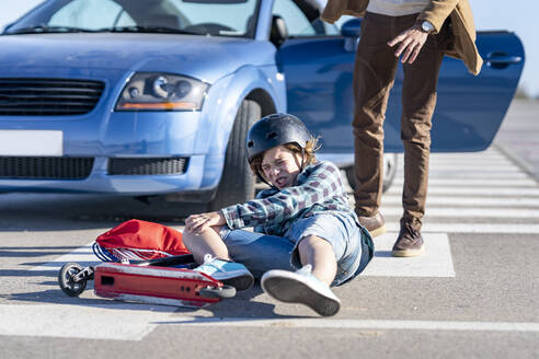 Boy falling down from push scooter with man standing by car on road after accident - GGGF00854