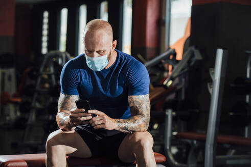 man with mask in gym using mobile phone - spain, andalucia, almeria - MIMFF00406