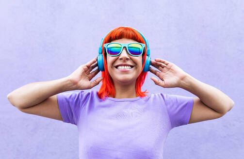 Happy stylish adult female with ginger dyed hair listening to music in headphones and singing along against violet wall in city - ADSF20036