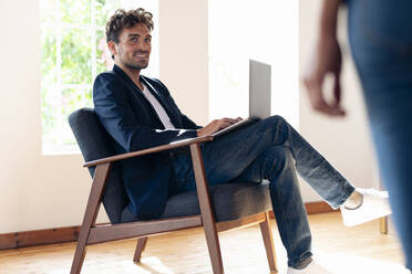 Smiling businessman looking at woman while working on laptop at home - SBOF02425