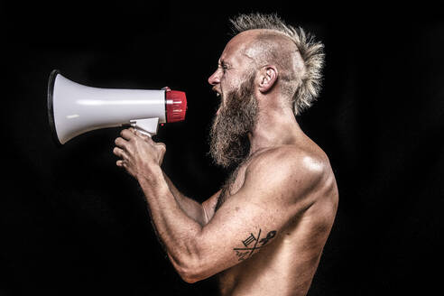 Angry male viking screaming while holding megaphone against black background - KBF00690