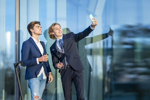 Smiling male professional taking selfie with coworker by glass on sunny day - GGGF00873