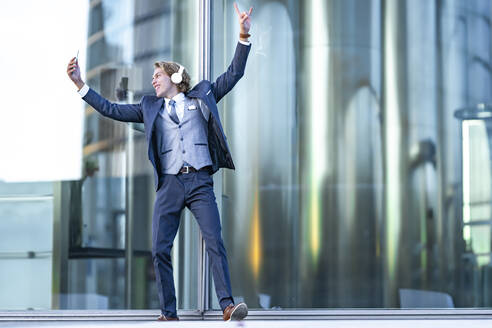 Male entrepreneur dancing while taking selfie and listening music against office building - GGGF00891