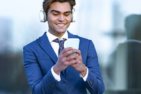 Happy male professional using smart phone while listening music against office building - GGGF00894