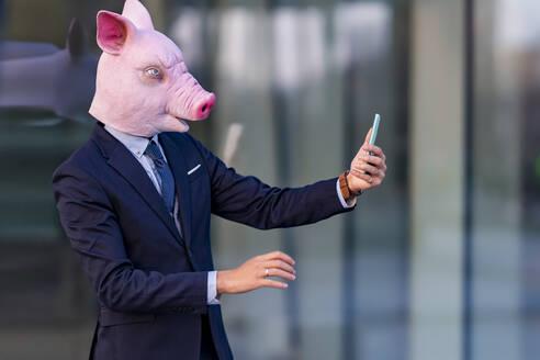 Male entrepreneur wearing pig mask on video call through smart phone - GGGF00900