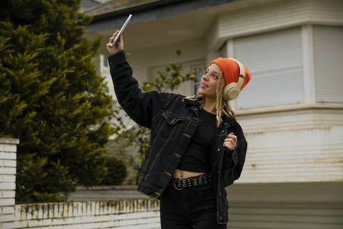 Young woman wearing knit hat taking selfie through smart phone against building - ACPF01042