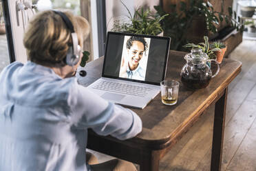 Senior woman having video call with granddaughter through laptop on table in living room - UUF22654