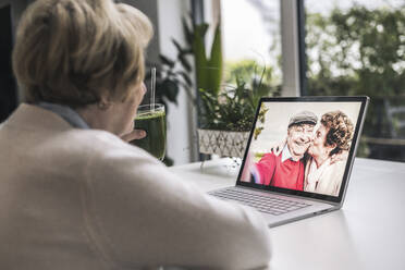 Senior woman on video call with friends through laptop at home - UUF22657