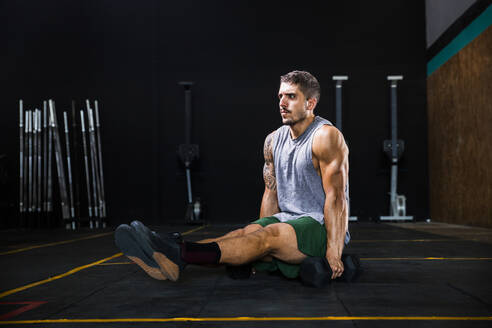 young man doing L-sit in a crossfit gym - spain, andalusia, almeria - MIMFF00415