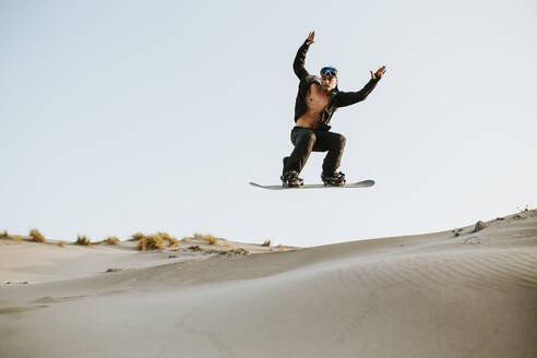 young man snowboarding on sand dunes - spain, andalusia, almeria - MIMFF00433