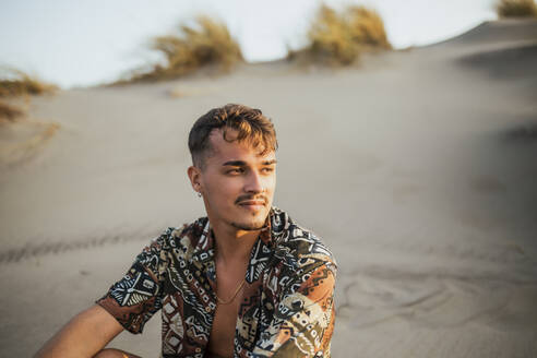 young man in open shirt sitting on dunes looking at horizon - spain, andalucia, almeria - MIMFF00439