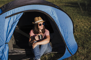 Beautiful woman wearing sunglasses with drink relaxing in tent - EBBF02191