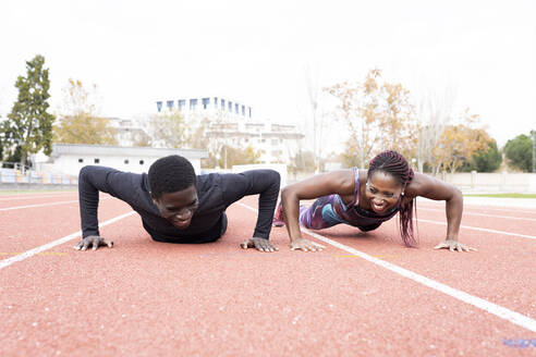Happy male and female sportsperson doing push ups on running track - JCCMF00867