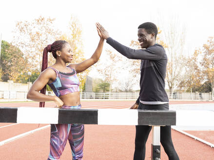 Male and female athlete giving high-five while standing by beam on running track - JCCMF00879