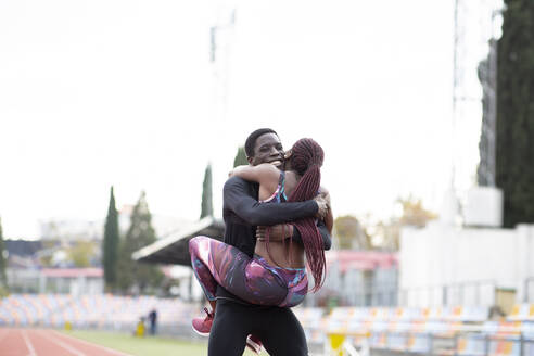 Young sportsman carrying sportswoman and embracing on track against clear sky - JCCMF00897