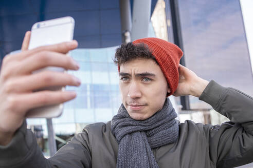 Young man adjusting knit while taking selfie through smart phone in city - IFRF00313