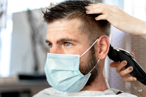 Side view of female master with trimmer cutting hair of male customer in protective mask during grooming procedure in salon at coronavirus pandemic time - ADSF20110