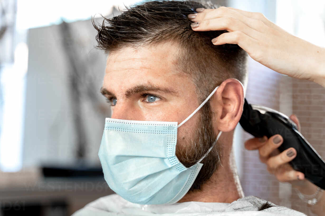 Side View Of Female Master With Trimmer Cutting Hair Of Male Customer In Protective Mask During