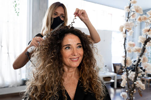 Professional hairdresser in black protective mask using curling tongs while making hairdo to long haired female customer in salon - ADSF20116