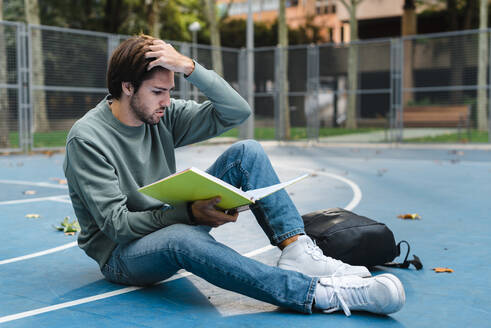 Young male student reading book while sitting at basketball court in university campus - JMPF00782