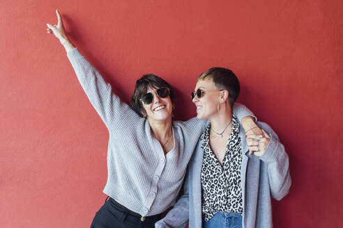Carefree woman smiling while standing with arm around on friend against red wall - JRVF00125