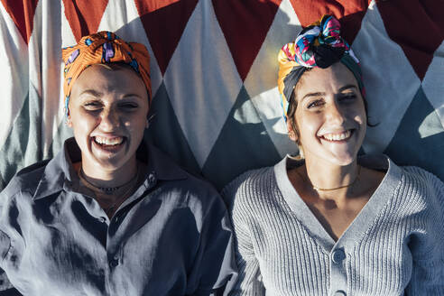 Young women wearing headscarf smiling while lying on blanket - JRVF00161