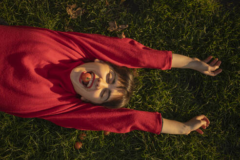 Happy girl wearing red laying on grass, Amsterdam, The Netherlands - AXHF00097