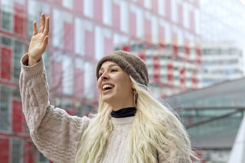 Cheerful young woman waving hand while standing against building in city - FLLF00574