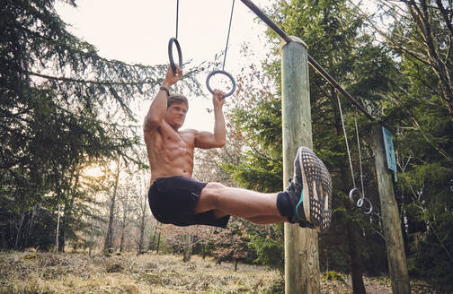 Shirtless male athlete hanging on gymnastic rings on fitness trail in forest - KDF00740