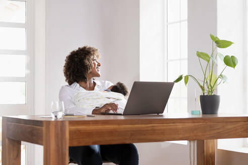 Woman with baby looking through window while sitting at home office - SBOF02467