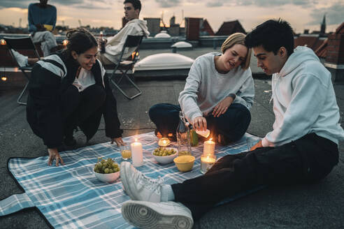 Male and female friends enjoying on building rooftop during sunset - MASF21356