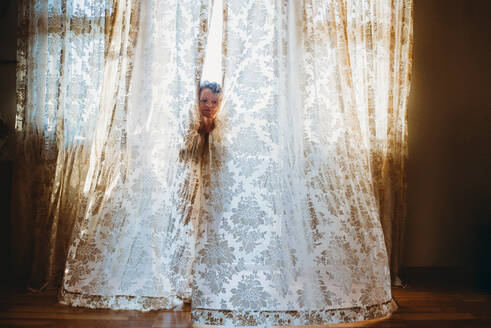 Little girl playing hide and seek with big vintage curtains at home - CAVF92013