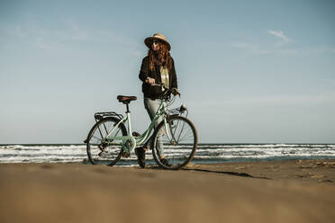 Young woman pushing bicycle while looking away against clear blue sky at Fangar beach - AFVF08076