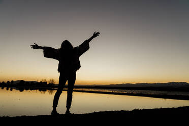 Young woman with arms outstretched standing by river during dusk at Ebro delta, Spain - AFVF08079